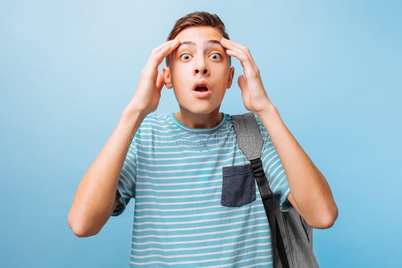 Niedergedrückter emotionaler Jugendkerl hebt seine Hände an und ruft hoffnungslos, ärgerlicher Gesichtsausdruck aus stockfoto