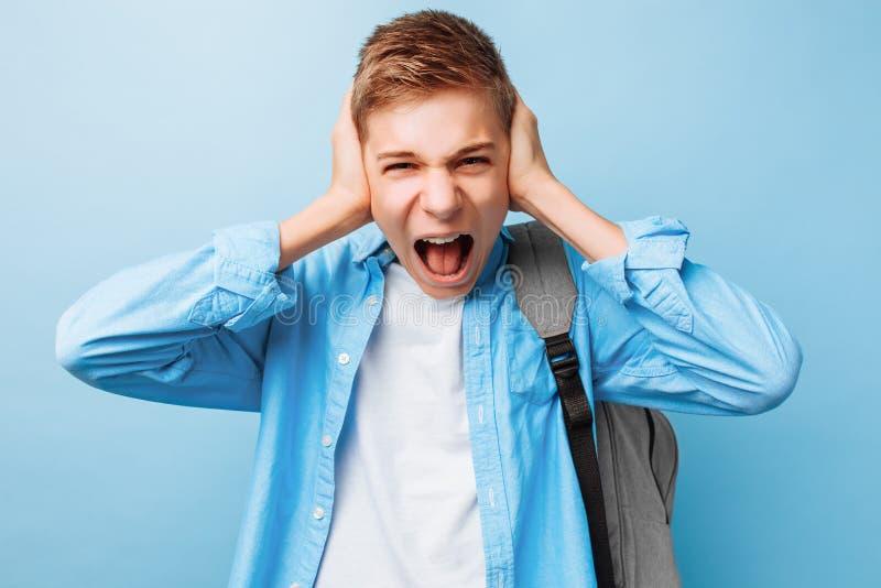 Niedergedrückter emotionaler Jugendkerl hebt seine Hände an und ruft hoffnungslos, ärgerlicher Gesichtsausdruck aus lizenzfreie stockfotos
