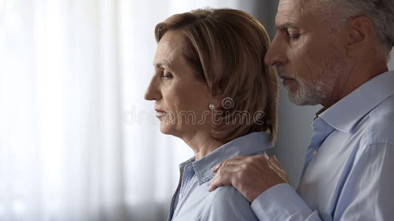 Niedergedrücktes alterndes bereitstehendes Fenster Dame, Gatte, der sie durch Schultern, Unterstützung nimmt lizenzfreies stockbild