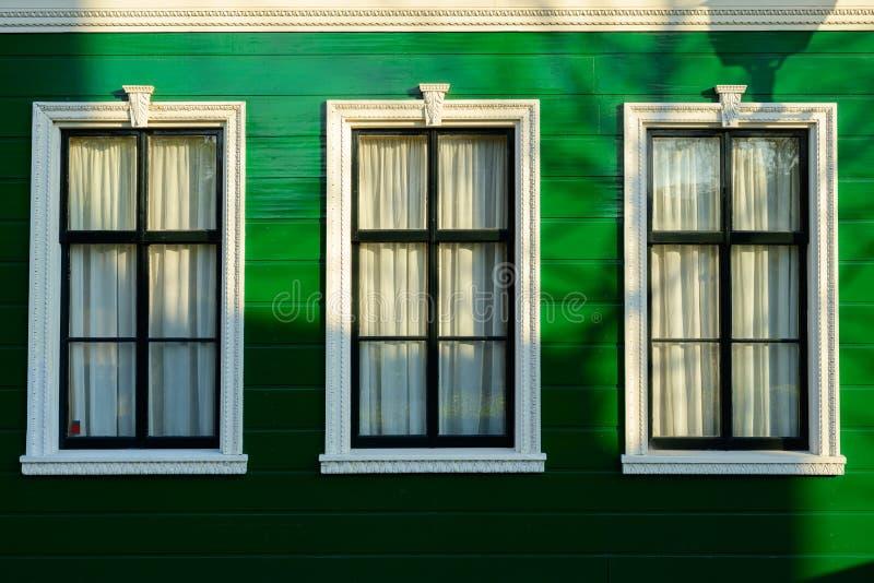Niederländische alte Hausarchitektur mit weißen Fenstern und grünen Wänden lizenzfreie stockbilder