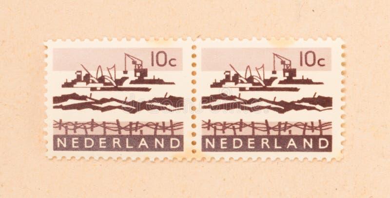NIEDERLÄNDISCHE 1970: Ein Stempel, der in den Niederlanden gedruckt wird, zeigt den Bau des afsluitdijk, circa 1970 stockbilder