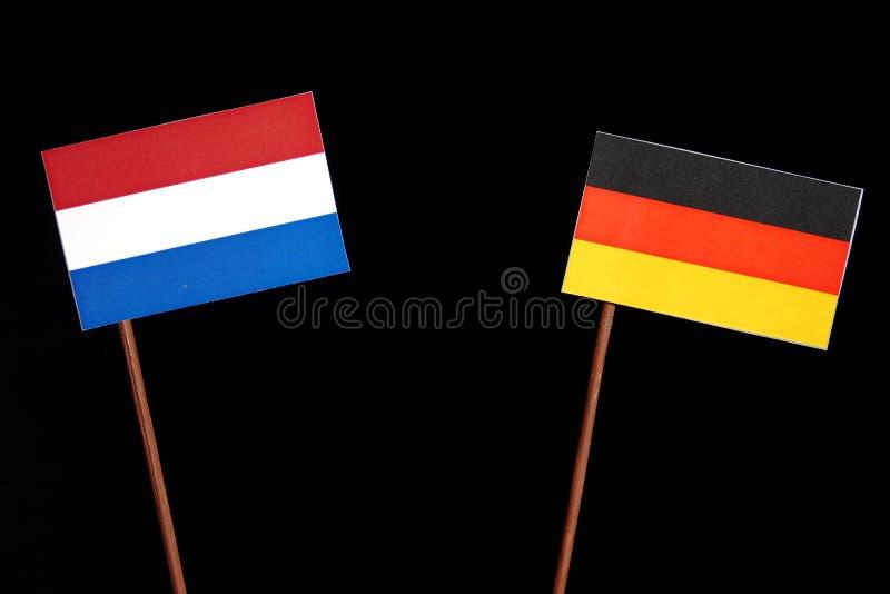Niederländische Flagge mit deutscher Flagge auf Schwarzem lizenzfreies stockfoto
