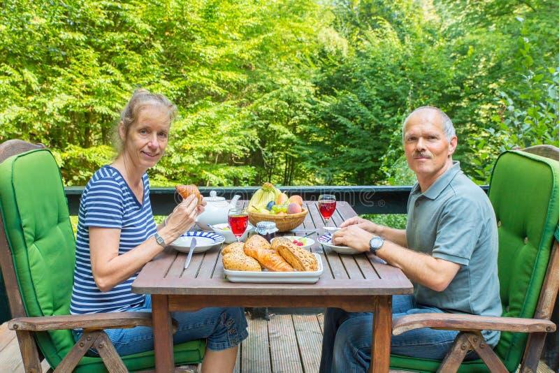 Niederländische Paare, die das Mittagessen auf Terrasse in der Natur essen lizenzfreie stockfotografie