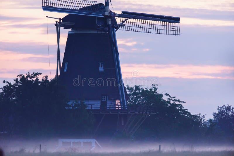 Niederländische Windmühle in der nebelhaften Landschaft stockbild
