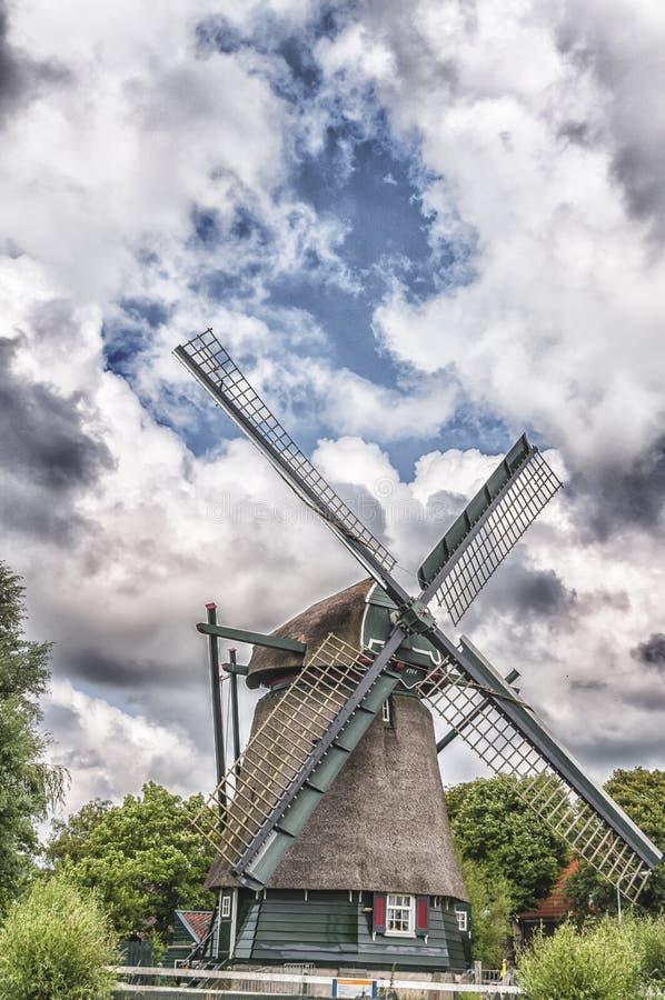 Niederländische Windmühle gegen einen bewölkten blauen Hintergrund stockbild