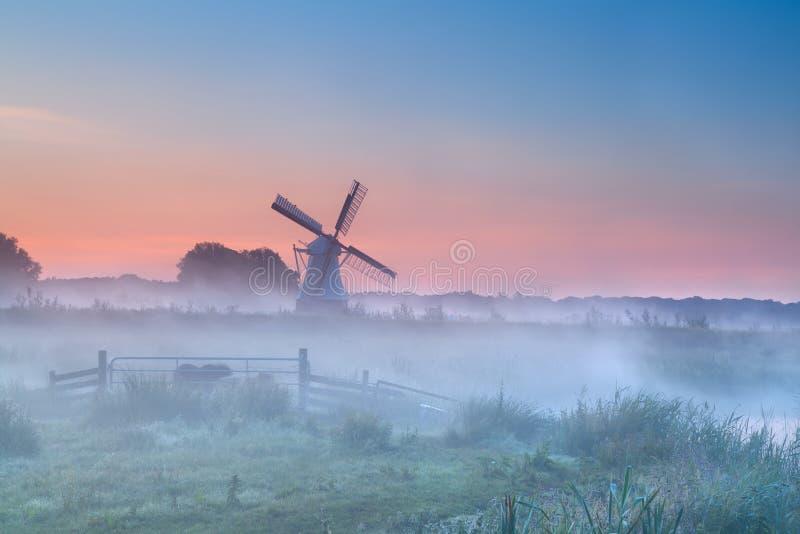 Niederländische Windmühle im dichten Morgennebel stockfotografie