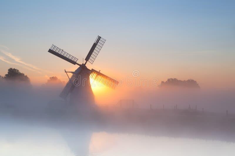 Niederländische Windmühle im dichten Nebel stockfotos