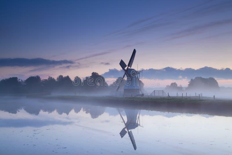 Niederländische Windmühle reflektierte sich im Fluss im Sonnenaufgangnebel stockfotos