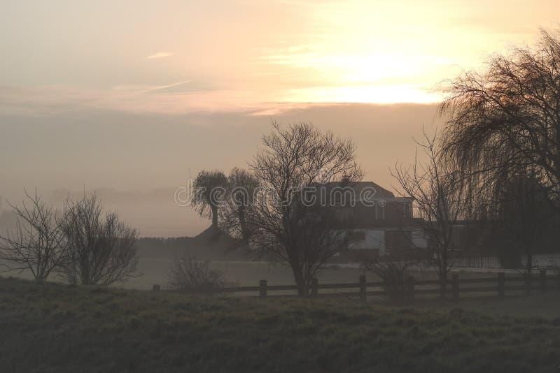 Niederländischer Bauernhof bei Sonnenaufgang auf einem nebelhaften Wintermorgen lizenzfreie stockfotos