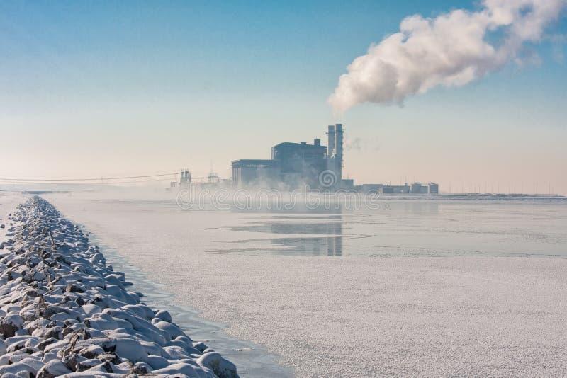 Niederländischer gefrorener See mit Dunst und Ansicht in Kraftwerk stockbilder