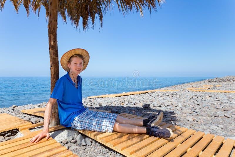 Niederländischer Junge, der unter Sonnenschirm auf portugiesischem Strand sitzt stockbilder