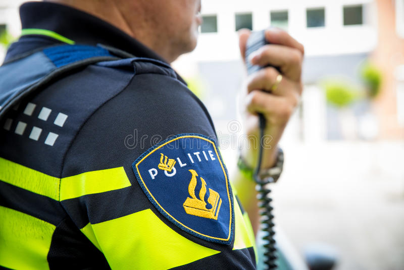 Niederländischer Polizist mit Radio Fokus auf Ausweis mit Logo lizenzfreie stockfotos