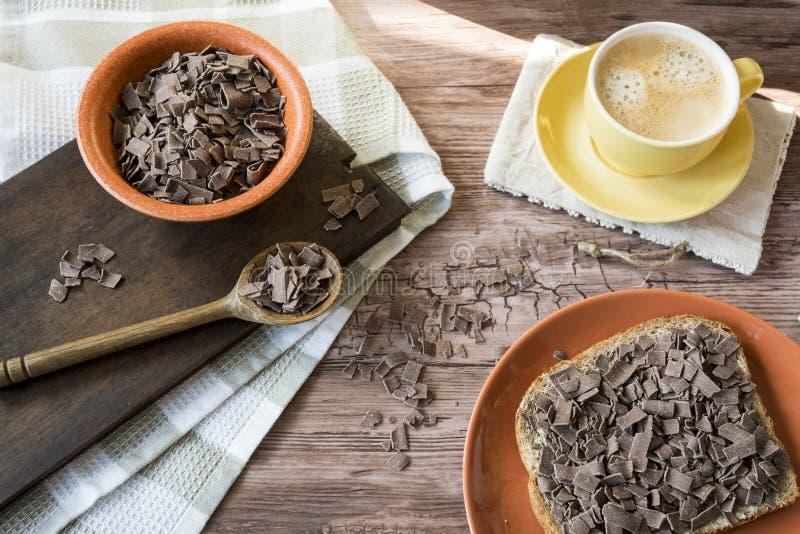 Niederländisches Frühstück mit ganzem graind Brot-Schokoladenhagel, Flocken und gelbem Becher Kaffee stockbilder