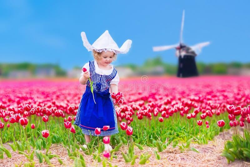 Niederländisches Mädchen im Tulpenfeld in Holland lizenzfreie stockfotos