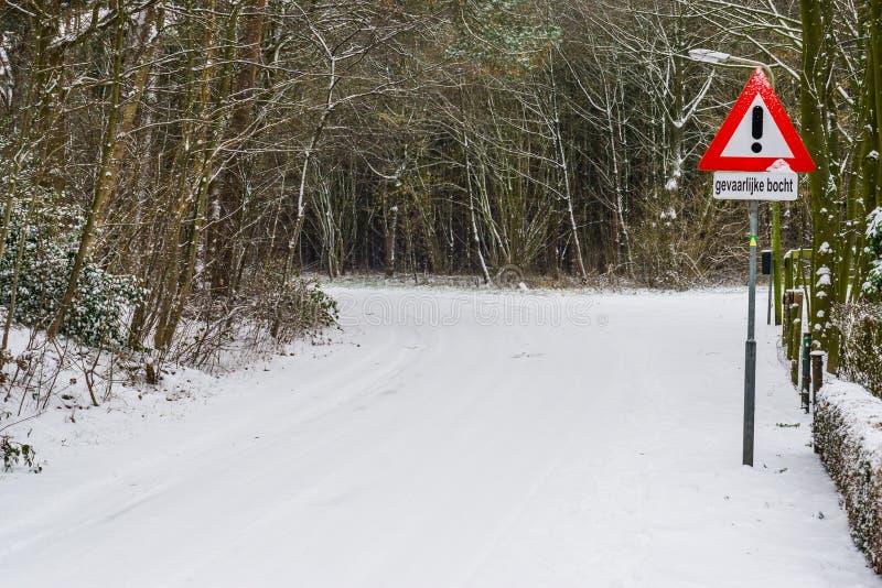 Niederländisches warnendes Verkehrszeichen, gefährliche Drehung in der ungünstigen Wetterbedingung, gefährliche Drehung der Vorsi stockfotografie