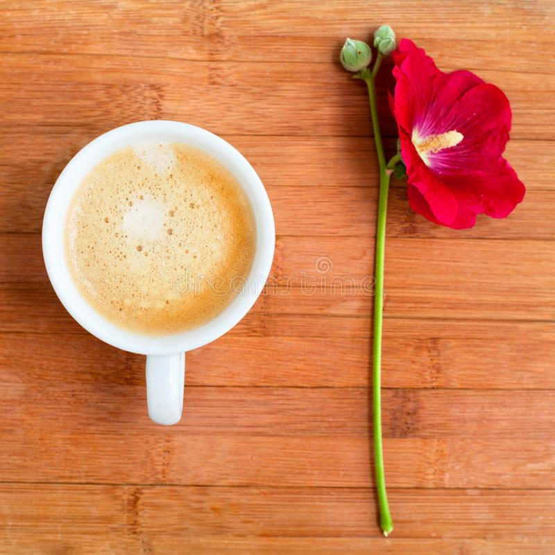 Niederlassung der roten Blume der Malve und der weißen Schale heißen Kaffees mit Schaum auf Tabelle auf hölzerner Hintergrundnaha stockfoto