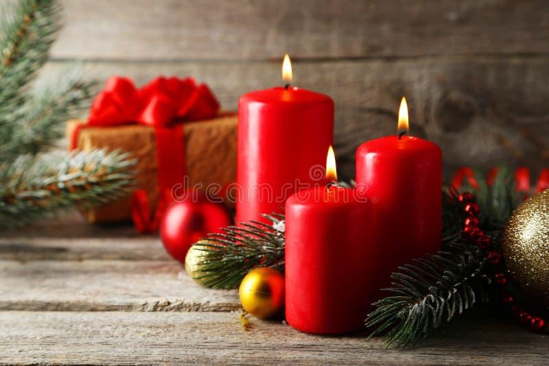 Niederlassung des Weihnachtsbaums mit Bällen und Kerzen auf hölzernem Hintergrund stockbilder