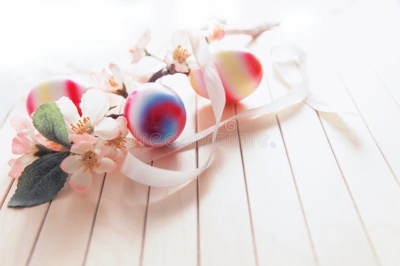 Niederlassung mit Frühlingsblumen und hellen Eiern lizenzfreie stockbilder