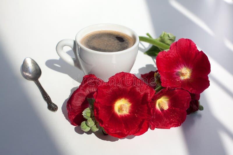 Niederlassung von roten Blumen der Malve und von weißer Schale schwarzem Kaffee mit Schaum, silbernes Sonnenlicht des Teelöffels  stockfoto