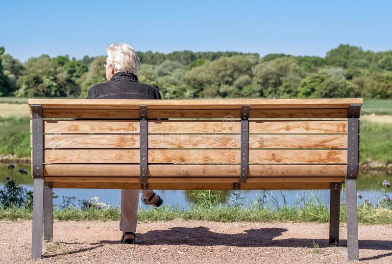 An elderly lady sitting alone on a park bench royalty free stock photography