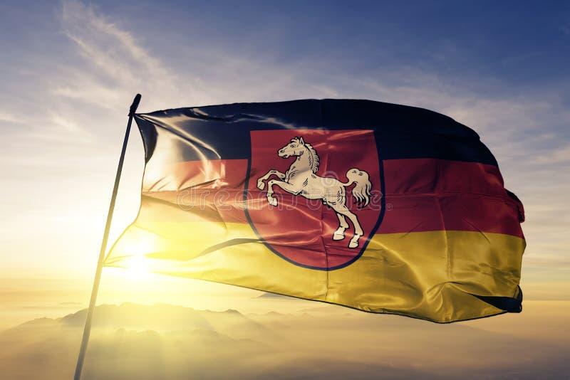 Niedersachsen-Staat des Deutschland-Flaggentextilstoffgewebes, das auf den Spitzensonnenaufgangnebelnebel wellenartig bewegt vektor abbildung