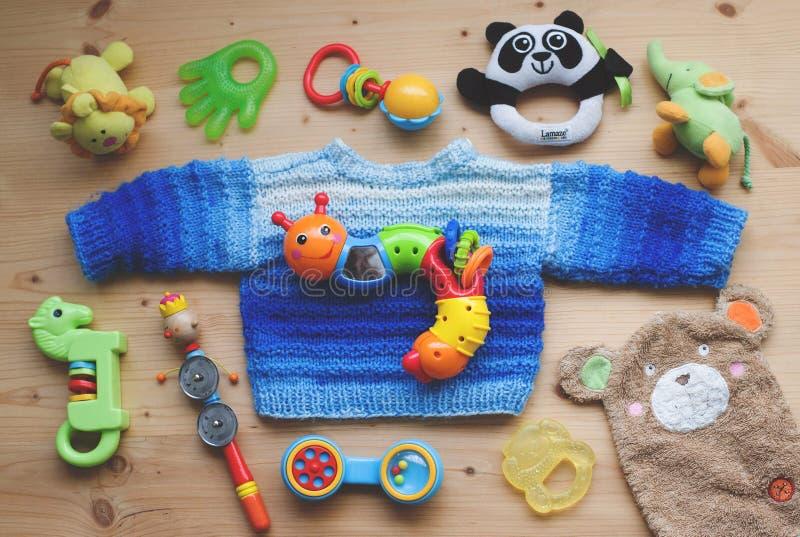 Niederstetten Tyskland, Februari 2018: Barnleksakerna och den hemlagade blåa tröjan som ligger på träbakgrund royaltyfri foto