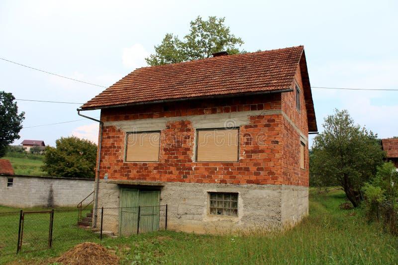 Niedokończony zaniechany czerwonej cegły rodziny dom z zamkniętymi nadokiennymi storami i niszczącymi drewnianymi garaży drzwiami obrazy stock