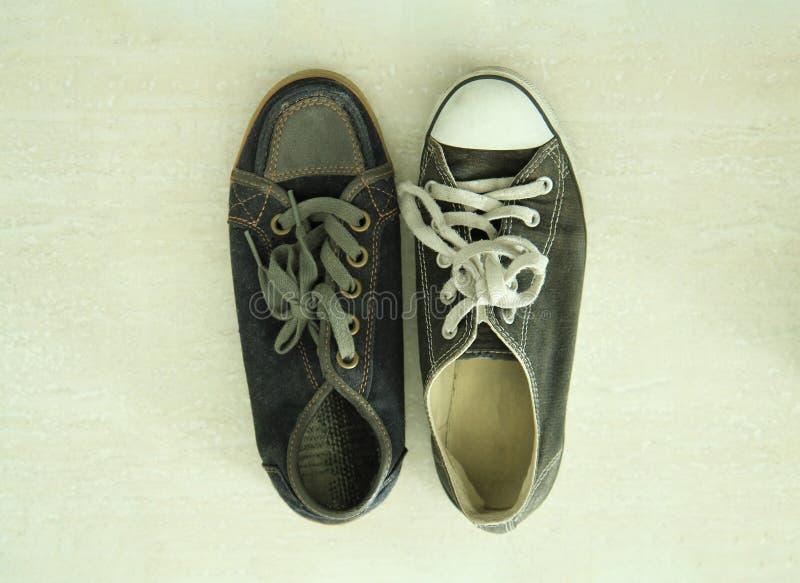 Niedopasowani czarny i biały sneakers zdjęcia stock