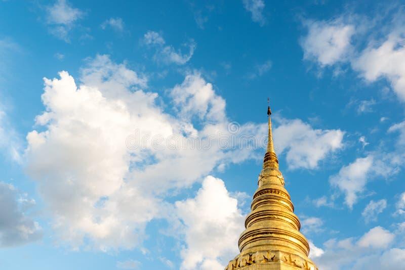 Niedrige goldene Pagode der Winkelsicht mit blauem Himmel und schöner Federwolke stockfotos