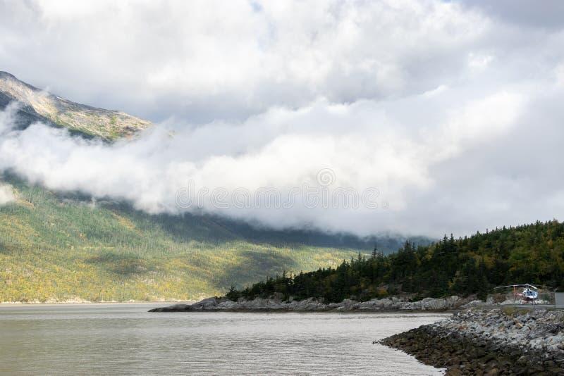 Niedrige hängende Wolken über Bergabhangküstenlinien in szenischem Skagway, Alaska lizenzfreie stockfotos
