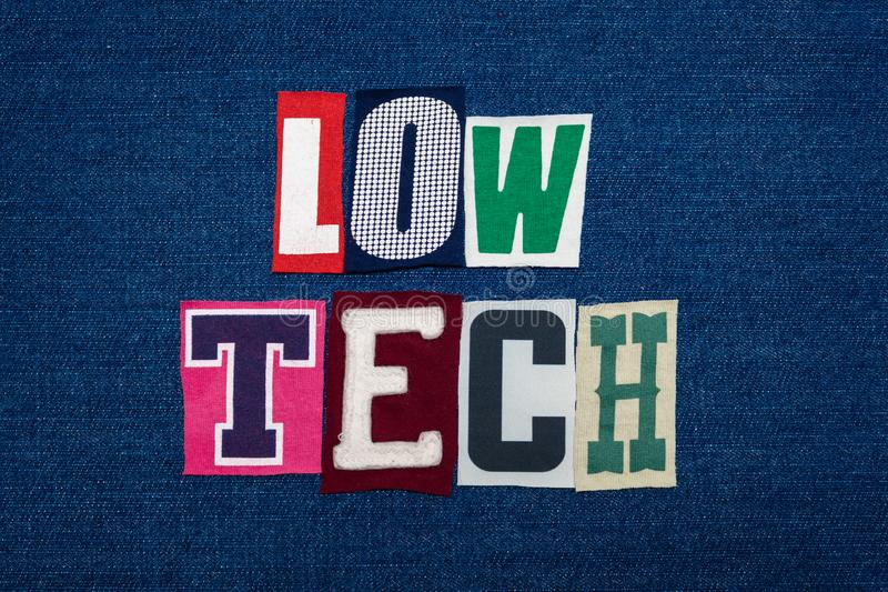 NIEDRIGE TECHNOLOGIE-Collage des Worttextes, multi farbiges Gewebe auf blauem Denim, einfaches Technologiekonzept stockfotos