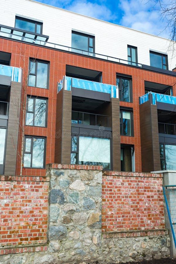 Niedrige Winkelsicht über modernes Wohnziegelsteinwohngebäudeäußeres mit großen Fenstern Moderner Appartementkomplex darunter lizenzfreie stockfotos