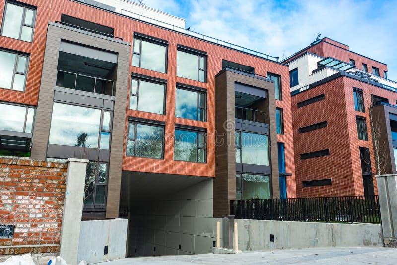 Niedrige Winkelsicht über modernes Wohnziegelsteinwohngebäudeäußeres mit großen Fenstern Moderner Appartementkomplex darunter lizenzfreies stockfoto