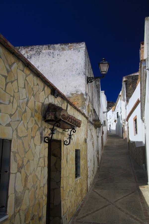 Niedrige Winkelsicht über schmale leere Gasse mit Fassaden von weißen Häusern und von Schritten, die oben zum dunkelblauen Himmel lizenzfreie stockfotos