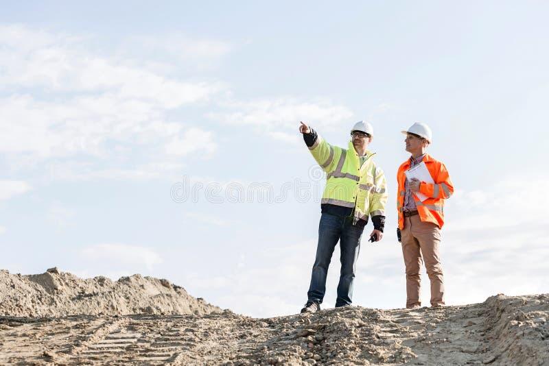 Niedrige Winkelsicht der Aufsichtskraft etwas an der Baustelle zeigend dem Kollegen stockbilder