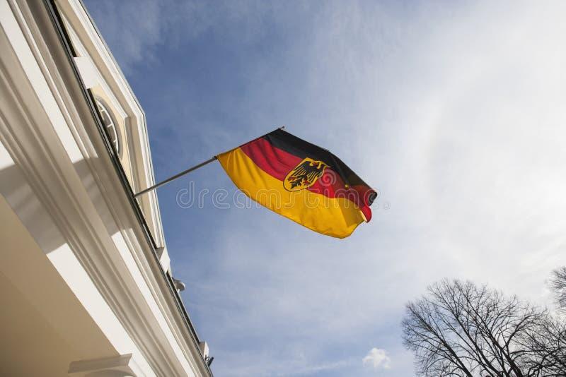 Niedrige Winkelsicht der deutschen Flagge auf Regierungsgebäude gegen bewölkten Himmel, Tallinn, Estland, Europa stockbilder