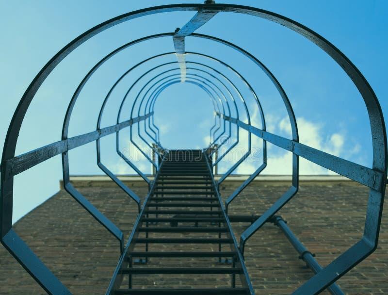 Niedrige Winkelsicht der Sicherheitskäfigleiter auf einer Backsteinmauer gegen blauen Himmel mit Wolken stockbilder