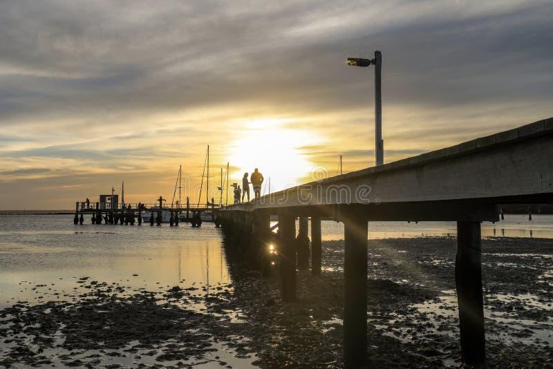 Niedrige Winkelsicht der Sonneneinstellung über Ozean und Pier stockfotografie