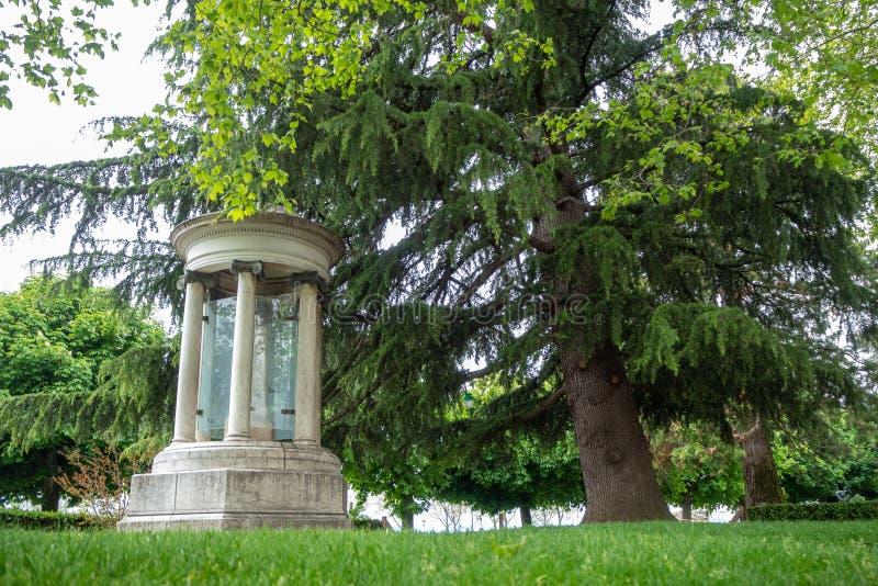 Niedrige Winkelsicht des schönen alten Steinmonuments mit großem üppigem grünem Park des Baums öffentlich stockfoto