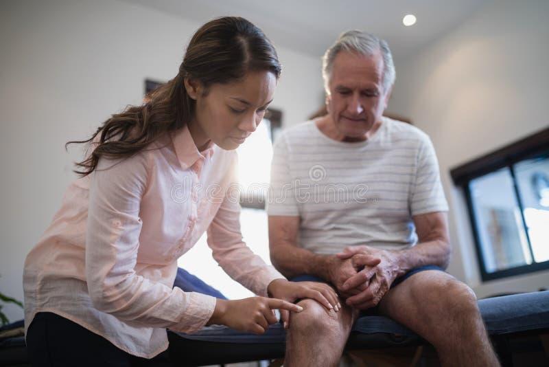 Niedrige Winkelsicht des Untersuchungsknies des weiblichen Therapeuten während männlicher Patient, der auf Bett sitzt stockbilder