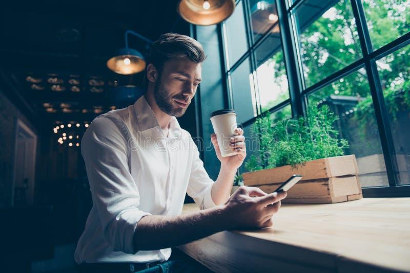Niedrige Winkelsicht eines hübschen Brünettekerlunternehmers, der eine Kaffeepause in einem Dachboden hat, redete das Restaurant  lizenzfreies stockbild