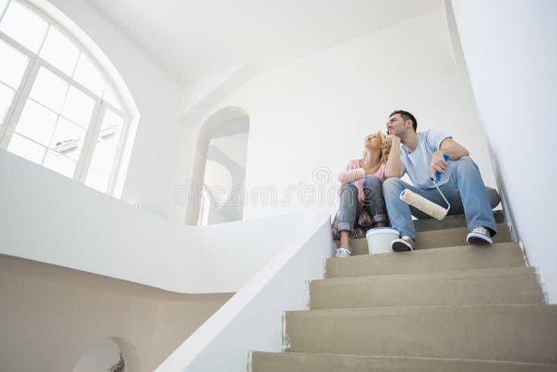 Niedrige Winkelsicht von Paaren mit Malerei bearbeitet das Sitzen auf Schritten im neuen Haus lizenzfreies stockfoto