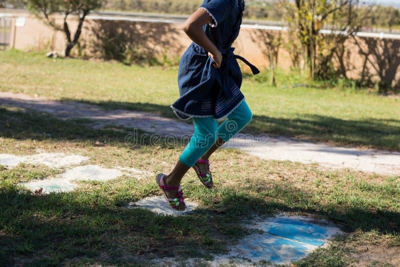 Niedriger Abschnitt des Mädchens springend auf grasartiges Feld stockfoto