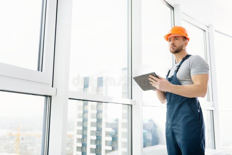 Niedriger Winkel des Berufsbauingenieurs, der Tablette verwendet stockbilder