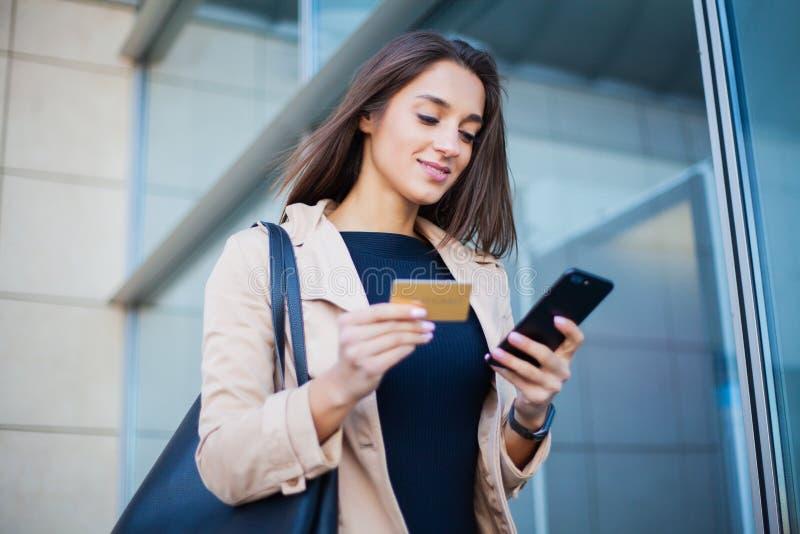 Niedriger Winkel des erfreuten Mädchens stehend am Flughafen Hall Er benutzt Goldkreditkarte und -Mobiltelefon für das Zahlen lizenzfreie stockfotos