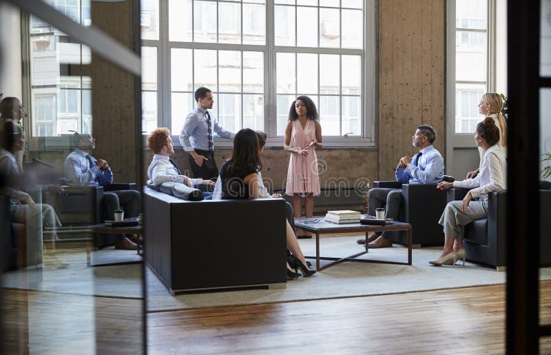 Nieformalny biznesowy spotkanie widzieć przez otwartych szklanych drzwi zdjęcie royalty free