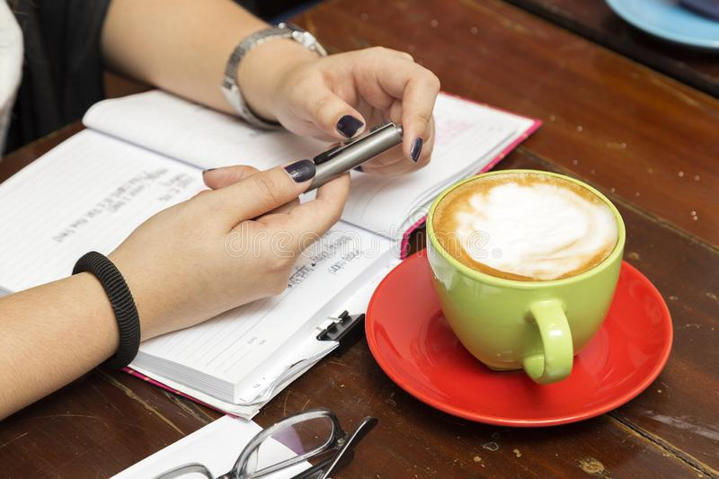 Nieformalny spotkanie: filiżanka kawy, notatnik, ręki i pióro na stole, zakończenie w górę obraz stock