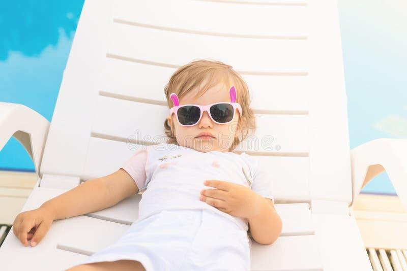 Niekończący się lato! Śliczny dziecko relaksuje przy sunbed blisko basenu, kurort fotografia royalty free