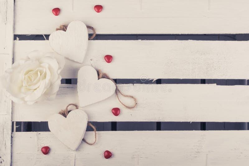 Niektóre biali drewniani serca na białym drewnie boksują tło obrazy royalty free