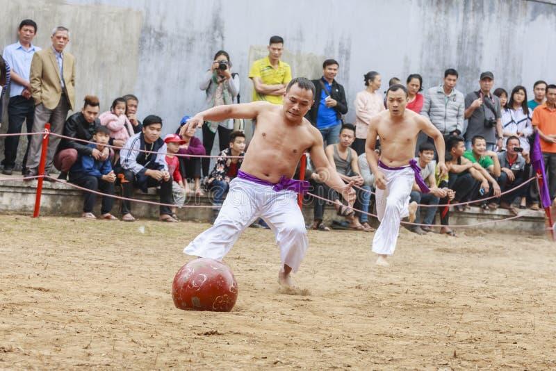 Niektóre młodzi człowiecy bawić się z drewnianą piłką w festiwalu księżycowym nowym roku przy Hanoi, Wietnam na Styczniu 27, 2016 fotografia stock